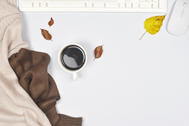 Sweater coat with cup of coffee and laptop, autumn leaves on white .