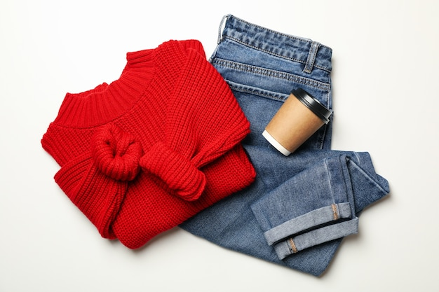 Sweater, jeans and paper cup on white background