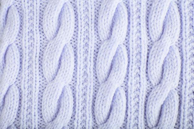 Свитер или фактура шарфа крупной вязки. вязаный фон из трикотажа с рельефным узором. косы в вязании. шерсть связана вручную или по схеме машинной вязки. предпосылка ткани.