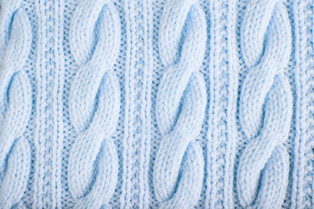 Sweater or scarf texture large knitting. knitted jersey background with a relief pattern. braids in knitting. wool hand-knitted or machine knitting pattern. fabric background.