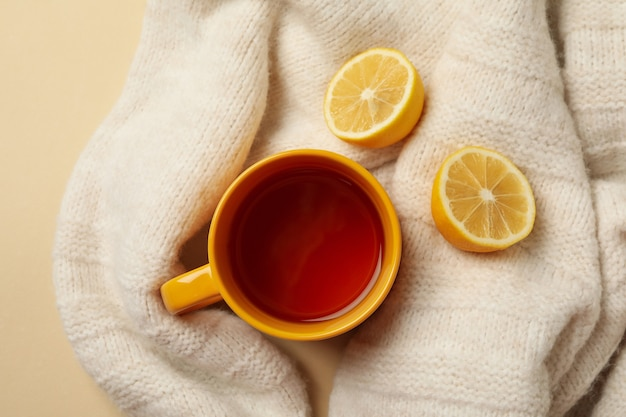 Sweater with cup of tea and lemons on beige background
