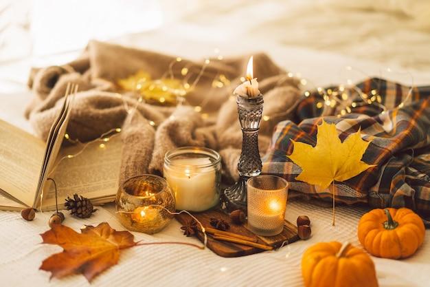 秋の装飾と本を読んだセーターとキャンドルは、家のインテリアの静物の詳細を読みます