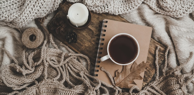 Sweaters and cup of tea with notebook, candle and knitting clothes