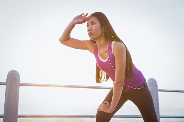 Sweating fit woman resting at promenade