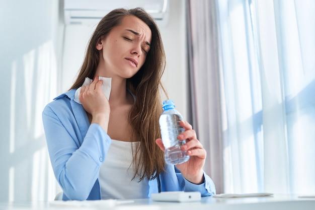 暑さ、暑さ、喉の渇きに苦しむ汗をかいた女性は、ナプキンで首を拭き、冷たいさわやかなウォーターボトルで体を冷やします。