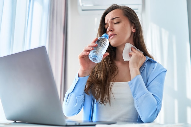 Sweating working woman suffering from hot weather and thirst wipes his neck with a napkin during online remote work at computer at home at summer day.