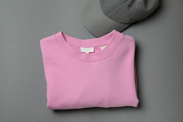 灰色の背景にスウェットシャツとキャップ