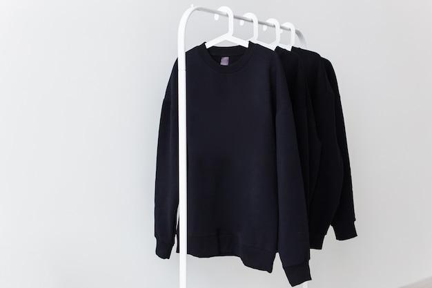 상점의 옷걸이에 걸려있는 스웨터와 후드.