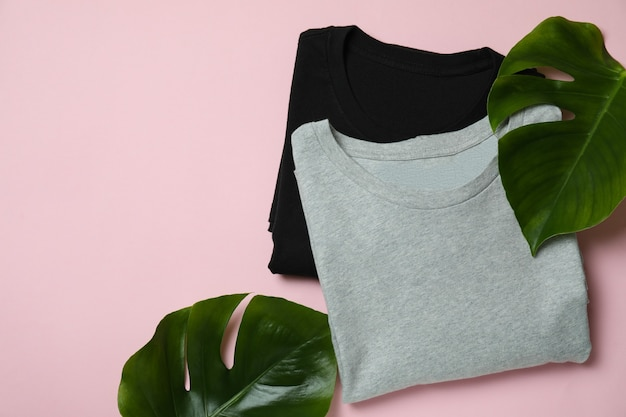 Sweatshirts and palm leaves on pink surface