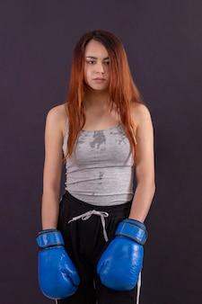 Потный боксер девушка с боксерскими перчатками стоя