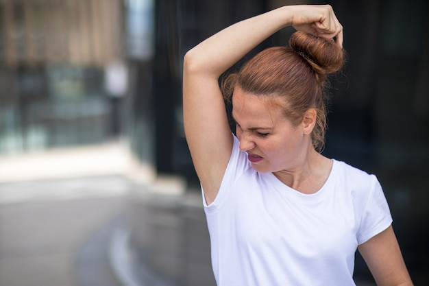 Sweaty girl sniffs her armpits in disgust