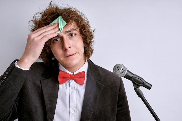 Sweaty male is afraid of bad presentation. stressed man with microphone , public speaker in suit isolated on white background. curly guy is afraid of giving speech for crowd of people or audience