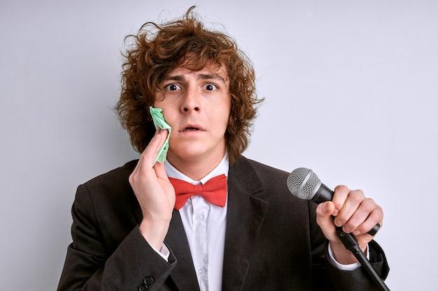 汗まみれの男性は悪いプレゼンテーションを恐れています。マイク、白い背景で隔離のスーツの演説者とストレスの多い男。巻き毛の男は、人々や聴衆の群衆のためにスピーチをすることを恐れています
