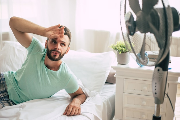 Sweaty young man is trying to refresh from the heat with a fan while lying in bed at home.