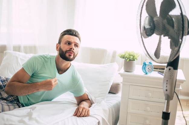 Потный молодой человек пытается освежиться от жары с вентилятором, лежа в постели у себя дома.