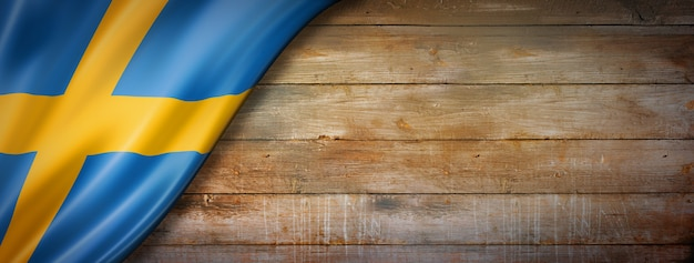 Sweden flag on vintage wood wall. horizontal panoramic banner.