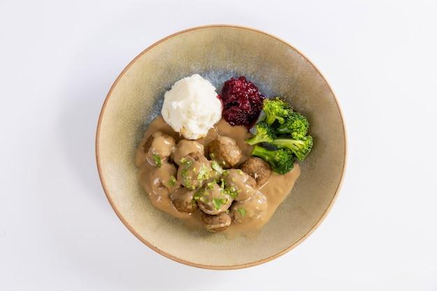 Шведские котлеты со сливочной подливкой, картофельным пюре и брусничным соусом.