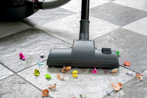 Подметите бумажные обрывки и пыль с кафельного пола с помощью пылесоса.