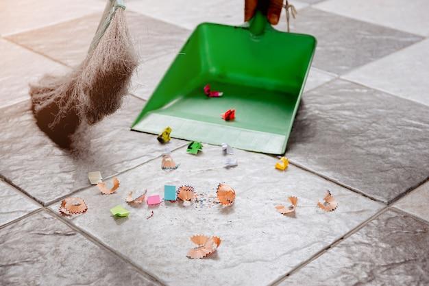 빗자루와 플라스틱 쓰레받기로 타일 바닥의 종이 조각과 먼지를 쓸어내십시오.
