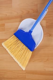 Sweeping broom with dustpan on wooden floor