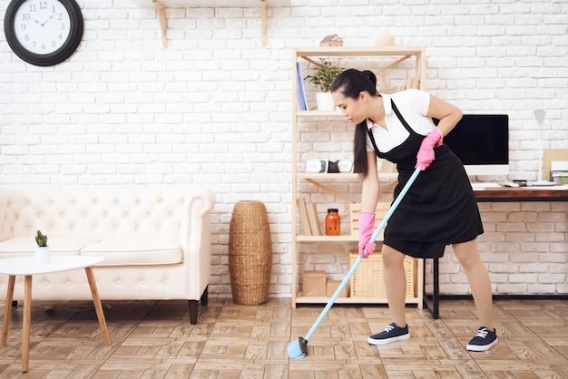 Sweeping floor with broom housekeeping service.