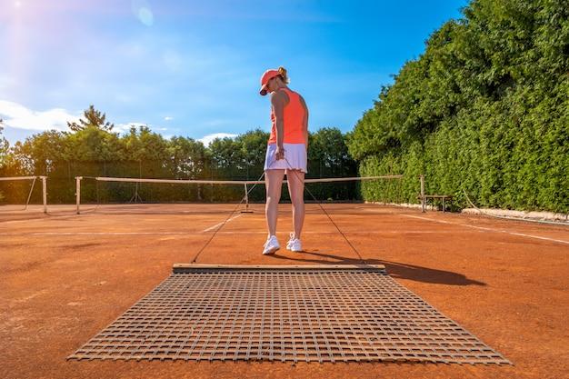 야외 테니스 코트에 오렌지 클레이 청소. 젊은 여성