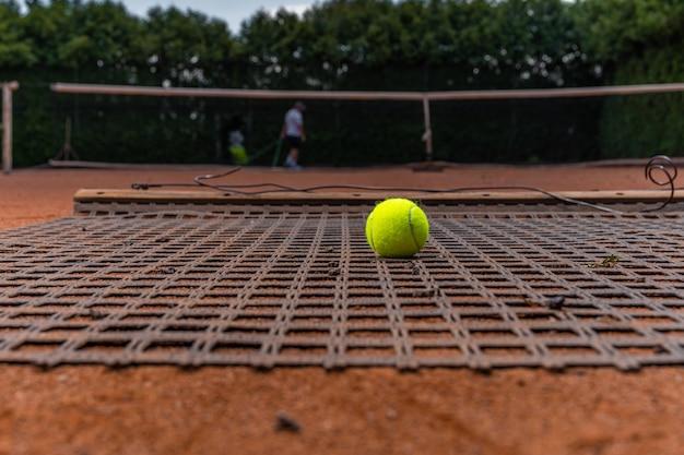 야외 테니스 코트에서 주황색 점토를 청소합니다.