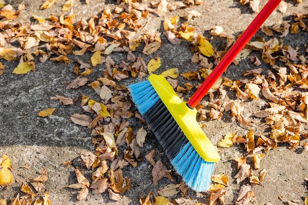 Подметать опавшие листья с земли в саду на переработку в течение осенне-осеннего сезона. человек подметает улицу, чтобы собрать сухие опавшие листья.