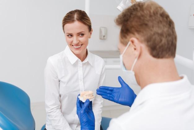 그녀의 치과 의사에게 방문을 지불하고 그의 상담을 구하면서 치과 위생에 대한 유용한 강의를받는 달콤한 사랑스러운 예쁜 여자