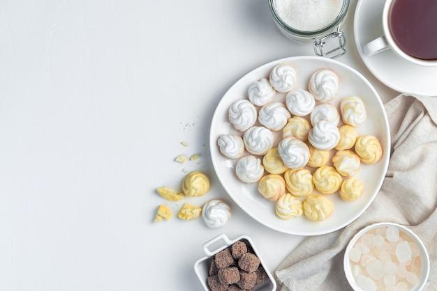 Сладкие воздушные безе белого и желтого цветов за чашкой чая. кулинарный фон с пространством для копирования.
