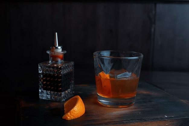 크리스탈 잔에 담긴 달콤한 알코올 시럽은 크리스탈 병 옆 술집의 테이블 위에 서 있습니다. 음료는 주황색 조각으로 장식되어 있습니다.
