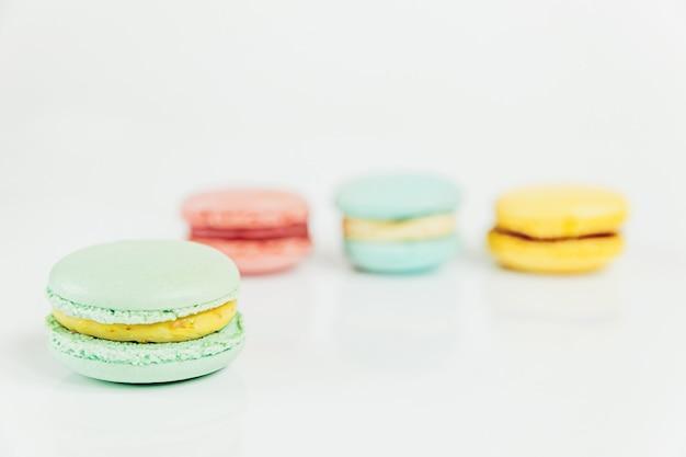 달콤한 아몬드 다채로운 파스텔 핑크 파란색 노란색 녹색 마카롱 또는 흰색 테이블에 고립 된 마카롱 디저트 케이크. 프랑스 달콤한 쿠키. 최소한의 음식 빵집 개념. 공간 복사