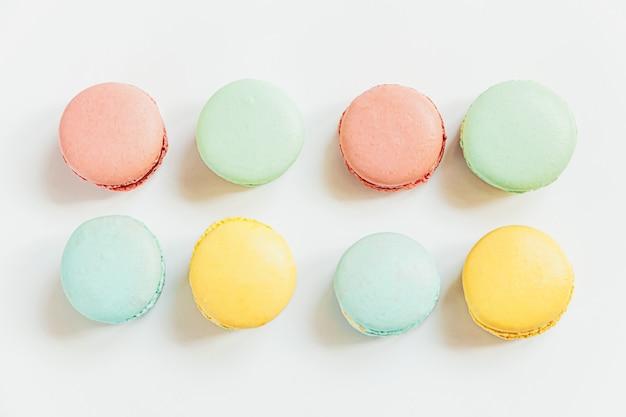 달콤한 아몬드 다채로운 파스텔 핑크 파란색 노란색 녹색 마카롱 또는 흰색 테이블에 고립 된 마카롱 디저트 케이크. 프랑스 달콤한 쿠키. 최소한의 음식 빵집 개념. 평면 위치 평면도, 복사 공간