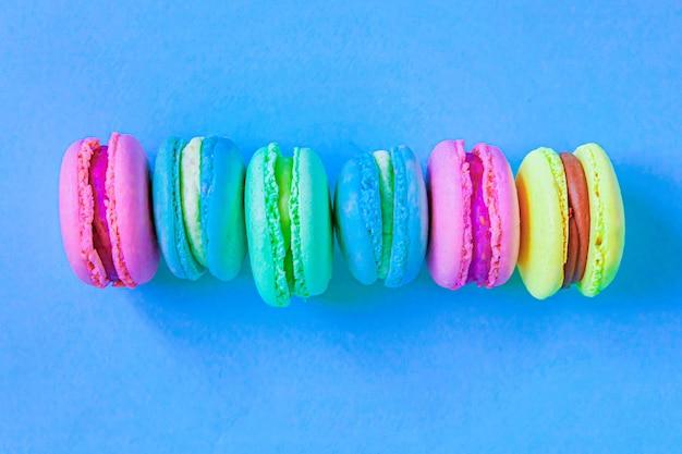 Сладкий миндаль красочный розовый синий желтый зеленый макарон или десертный торт макарун, изолированные на модном синем пастельном фоне.
