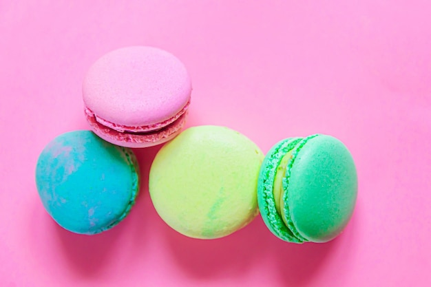 Сладкий миндаль красочный розовый синий желтый зеленый макарон или десертный торт макарун, изолированные на модном розовом пастельном фоне.