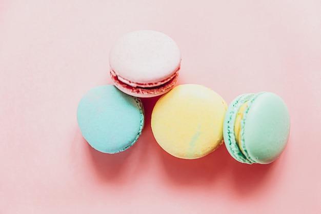 달콤한 아몬드 화려한 분홍색 파란색 노란색 녹색 마카롱 또는 유행 핑크 파스텔 테이블에 고립 된 마카롱 디저트 케이크. 프랑스 달콤한 쿠키. 최소한의 음식 빵집 개념. 평면 위치 평면도, 복사 공간