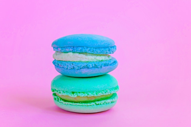 トレンディなピンクのパステルカラーの背景に分離された甘いアーモンドカラフルなユニコーンブルーグリーンマカロンまたはマカロンデザートケーキ。