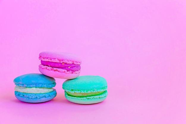달콤한 아몬드 다채로운 유니콘 블루 그린 핑크 마카롱 또는 트렌디 한 핑크 파스텔 테이블에 고립 된 마카롱 디저트 케이크. 프랑스 달콤한 쿠키. 최소한의 음식 빵집 개념. 공간 복사