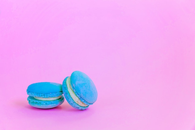 달콤한 아몬드 다채로운 유니콘 블루 마카롱 또는 유행 핑크 파스텔 테이블에 고립 된 마카롱 디저트 케이크. 프랑스 달콤한 쿠키. 최소한의 음식 빵집 개념. 공간 복사