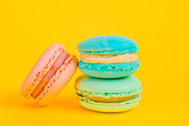 Sweet almond colorful unicorn blue pink macaron or macaroon dessert cake isolated on trendy yellow modern fashion