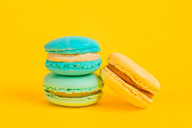 Sweet almond colorful unicorn blue yellow macaron or macaroon dessert cake isolated on trendy yellow modern fashion background. french sweet cookie. minimal food bakery concept. copy space