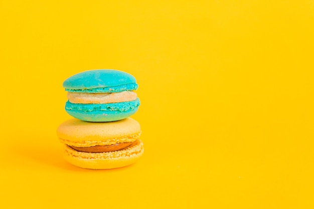 Sweet almond colorful unicorn blue yellow macaron or macaroon dessert cake isolated on trendy yellow modern fashion