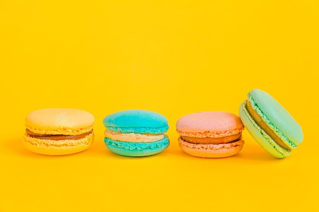Сладкий миндаль красочный единорог розовый синий желтый зеленый макарон или десертный торт макаруны, изолированные на модном желтом фоне современной моды. французское сладкое печенье. минимальная концепция пекарни еды. копировать пространство