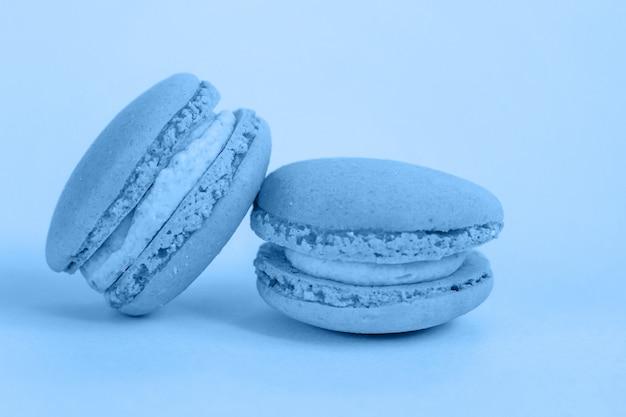 甘いアーモンドマカロンまたはマカロンデザートケーキは、2020年のトレンディな色に着色されたクラシックブルーブルーパステル背景に分離されました。色を使用したマクロ。 copyspace。