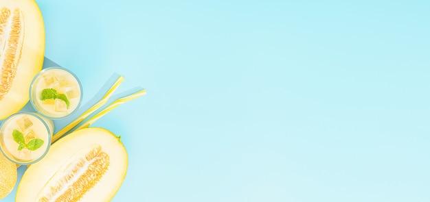 スライスしたメロンを背景にグラスに入ったメロンの甘くて冷たいジュース