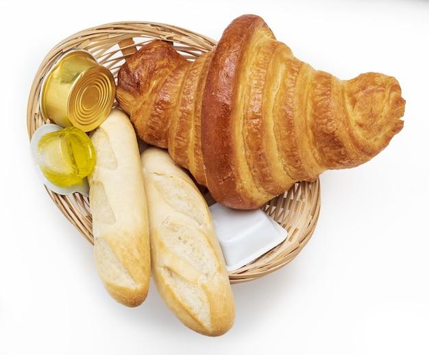 Сладко-соленый завтрак. плетеная корзина с круассаном, булочками, оливковым маслом и джемом. изолированный.