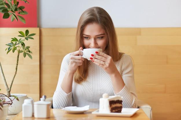 甘く誠実な女性は地元のカフェで時間を過ごし、昼食時に休憩し、白いカップで温かい飲み物を飲みます。