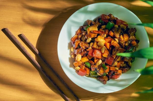 Кисло-сладкий цыпленок с овощами вок, кунжутом, арахисом и сычуаньским перцем в белой миске. китайская кухня