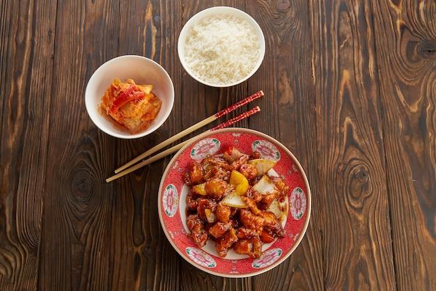 ピーマン、タマネギ、パイナップルを添えた甘酸っぱい揚げ豚肉のチャンク、箸を使った赤いプレート、白いボウルにご飯を入れた古い木製のテーブル、伝統的なスープ、アジア料理のコンセプト