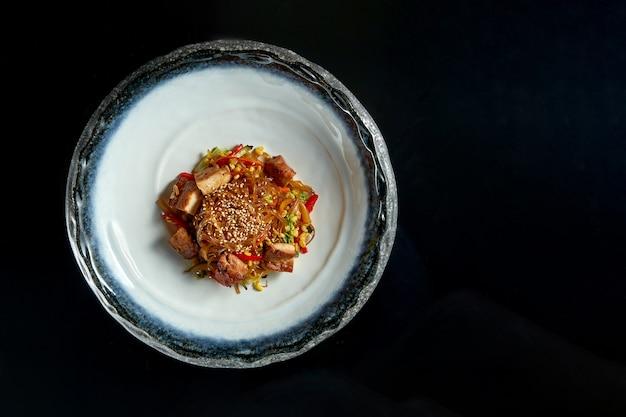 Кисло-сладкая стеклянная лапша со свининой, овощами и луком, подается в белой миске.